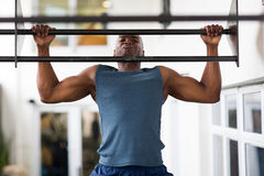 African man pull-ups. Strong african man doing pull-ups on a bar in a gym Royalty Free Stock Photos