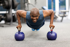 African man push-ups. Happy young african man doing push-ups exercise with kettle bells Royalty Free Stock Images