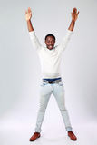 African man with raised hands. Full length portrait of african man with raised hands on gray background Royalty Free Stock Images