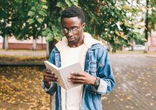 african man reading book in autumn city park royalty free stock photos