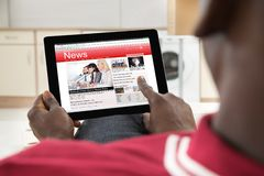 African Man Reading News On Digital Tablet Royalty Free Stock Photos