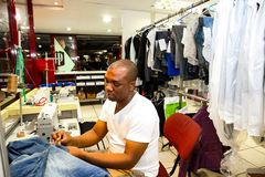 African Man repairing clothes at a Dry Cleaner. Johannesburg, South Africa - April 27 2011: African Man repairing clothes at a Dry Cleaner stock photography