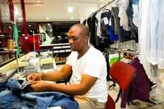 African Man repairing clothes at a Dry Cleaner. Johannesburg, South Africa - April 27 2011: African Man repairing clothes at a Dry Cleaner royalty free stock image