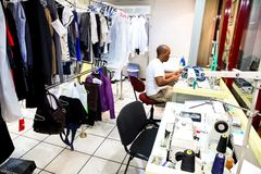 African Man repairing clothes at a Dry Cleaner. Johannesburg, South Africa - April 27 2011: African Man repairing clothes at a Dry Cleaner stock photos