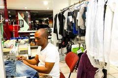 African Man repairing clothes at a Dry Cleaner. Johannesburg, South Africa - April 27 2011: African Man repairing clothes at a Dry Cleaner royalty free stock photography