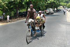African man rides his  tricycle with body. Royalty Free Stock Photo
