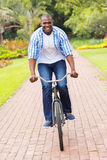 African man riding bicycle. Happy african american man riding bicycle outdoors Stock Photos