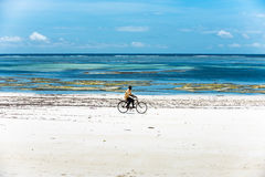 African man riding a bike on the beach Royalty Free Stock Photography