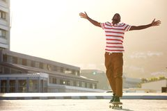 African man riding skateboard on street Royalty Free Stock Photography