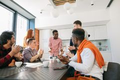African man with serious face telling amusing anecdotes to co-workers. African men with serious face telling amusing anecdotes to co-workers in break time Stock Photo