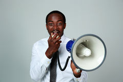 African man shouting through a megaphone. On gray background Royalty Free Stock Image