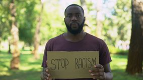 African man showing stop racism sign, national problem, equal rights, abuse