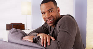 African man sitting on couch smiling Stock Photo