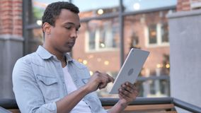 African man sitting outdoor and using tablet stock video