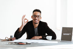 African man sitting by the table and showing ok sign. African man in suit and eyeglasses sitting by the table with cup of coffee and  retro camera while showing Royalty Free Stock Photos