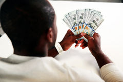 African man sitting with US dollars Royalty Free Stock Photo