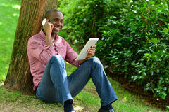 African man with smart phone and tablet Royalty Free Stock Photography