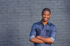 African man smiling against gray wall with blue shirt Stock Photo