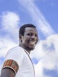 African man smiling in front of a blue sky Royalty Free Stock Image