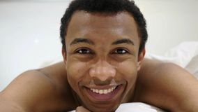 African Man Smiling and Looking in Camera, Laughing in Bed stock photos