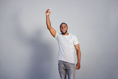 African man smiling with phone in hand against gray wall Royalty Free Stock Photography