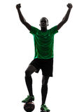 African man soccer player  celebrating victory silhouette. One african man soccer player celebrating victory green jersey in silhouette  on white background Royalty Free Stock Photo