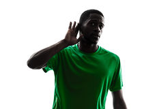 African man soccer player silhouette hearing gesture. One african man soccer player green jersey hearing gesture in silhouette on white background stock image