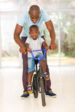 African man son bike. Happy african men helping his son to ride a bike indoors royalty free stock photo