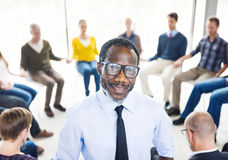 African Man Standing in Front of a Support Group.  royalty free stock photography