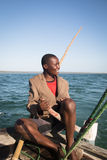 African man stearing a boat near Tofo Stock Photo