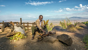 African man in a suit sells corn  near the Great Rift Valley in Stock Photo