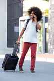 African man with suitcase talking on cellphone in city Royalty Free Stock Photos