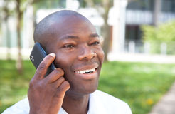 African man talking at phone outside in a park. With meadow, trees and a building in the background Royalty Free Stock Photo