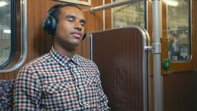 African man in a train car of the Berlin subway listening to music on headphones with pleasure. African man in a train car in the Berlin subway listening to stock video