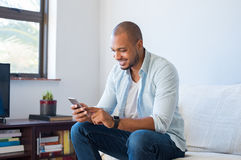 African man typing phone message. Happy black man using smart phone at home. Smiling young african man at home sitting on couch reading phone message. Handsome Stock Images