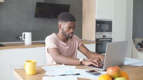 African man using laptop while caucasian girlfriend standing lonely at kitchen stock footage