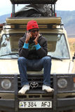 African Man using phone on Safari Truck. An African man talking on the cell phone on a safari truck royalty free stock images