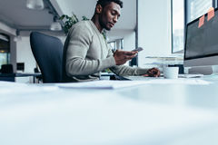 African man using smart phone. While sitting at work place. Businessman sitting in modern office Royalty Free Stock Photo