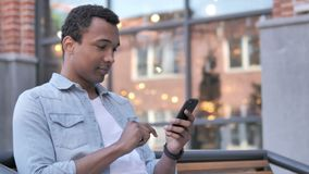 African man using smartphone sitting outdoor stock video