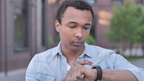 African Man Using Smartwatch Outdoor. 4k high quality, 4k high quality stock footage