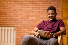 African man using tablet for video conversation while relaxing on armchair. In modern office. Concept of young business people working at home Stock Photography