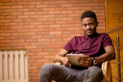 African man using tablet for video conversation while relaxing on armchair. In modern office. Concept of young business people working at home Royalty Free Stock Image