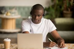 African man wearing headphones watching webinar making notes study online