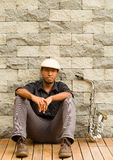 African man wearing sixpence hat and dark shirt sitting down leaning against wall, saxophone next to him Royalty Free Stock Images