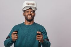 African man wears virtual reality goggles, holds game controllers, isolated stock photography