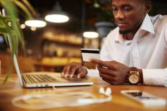 African businessman paying with credit card. Royalty Free Stock Photos