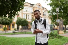 African student walking at park and using call phone. African man in white shirt using smart phone looking away. Handsome male student walking at park, writing Stock Photography
