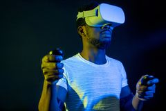 African Man in white, wearing VR Headset on green blue dual color background. stock photo