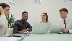 African manager is presenting the results of his report to his colleagues in co-working room. stock footage