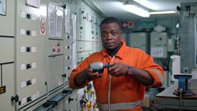 African marine engineer officer in engine control room ECR.  stock video